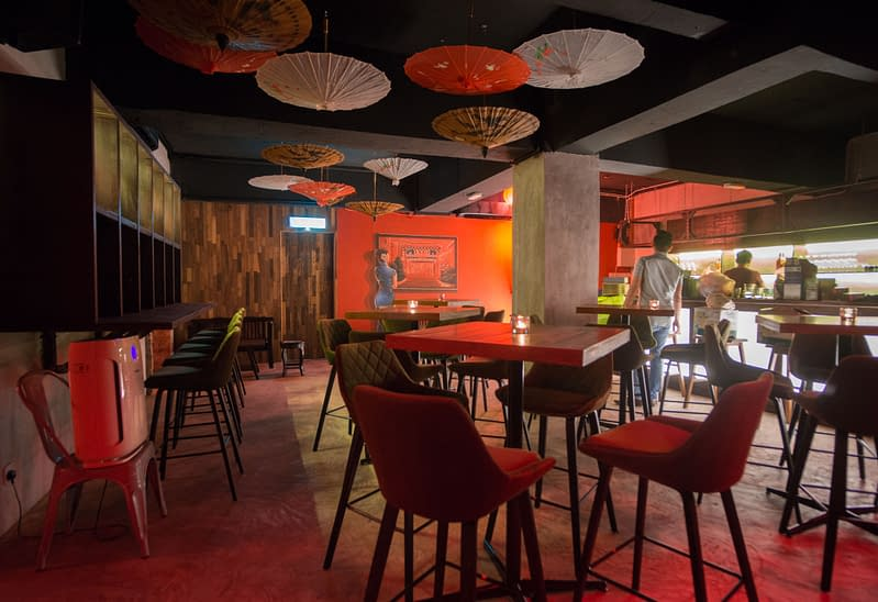 Red themed oriental interior design of a hidden bar in Kuching with an eerie mural