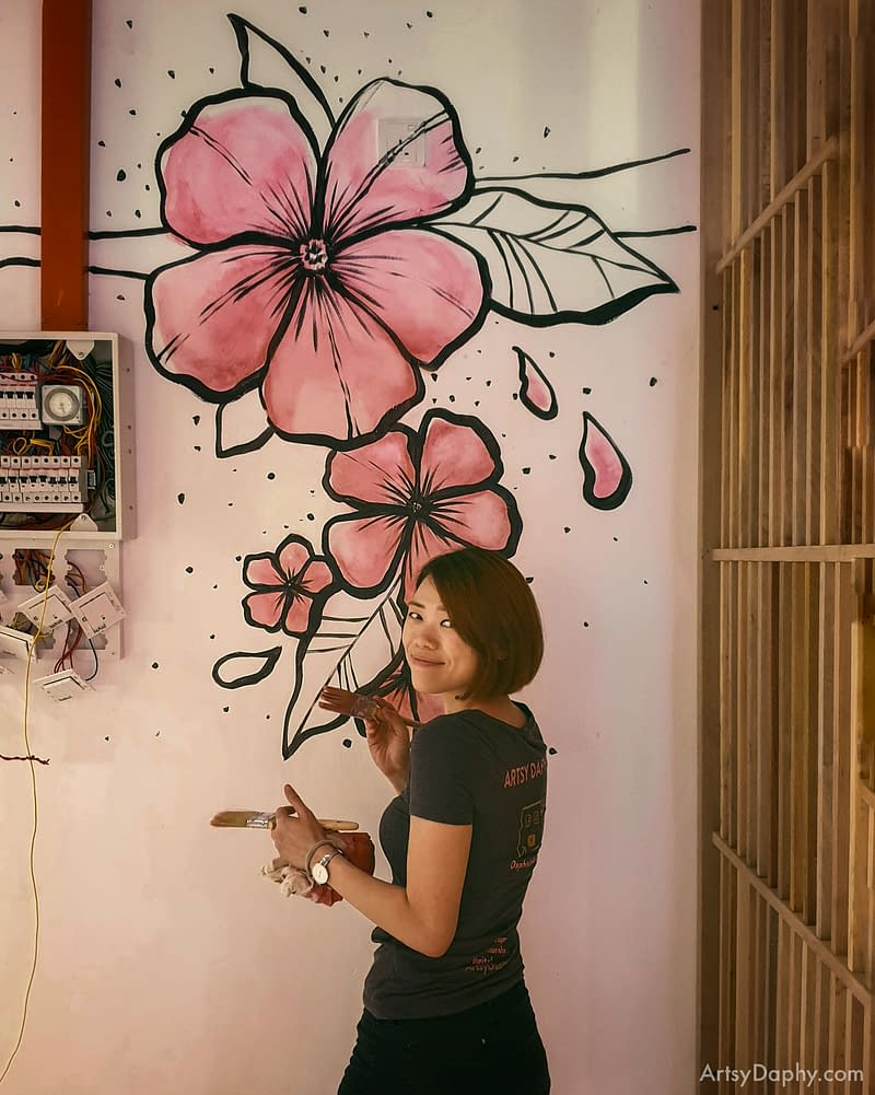 Artsy Daphy painting a watercolour style painting of flowers on the wall