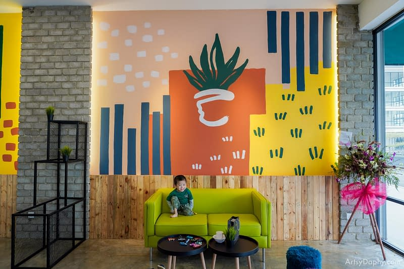 A young kid hanging out on a sofa in front of the Grass Dessert Colourful Murals