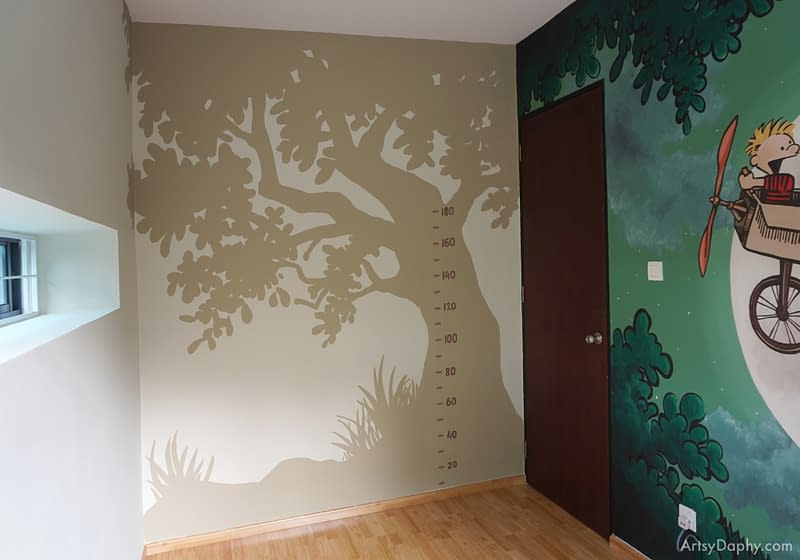 a measurement wall in a kids room with a silhouette of a tree in the background
