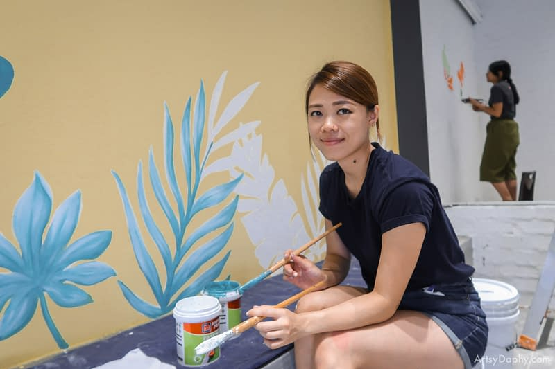 smiling Artsy Daphy painting tropical mural at Ono Poke bowl store with nippon pain