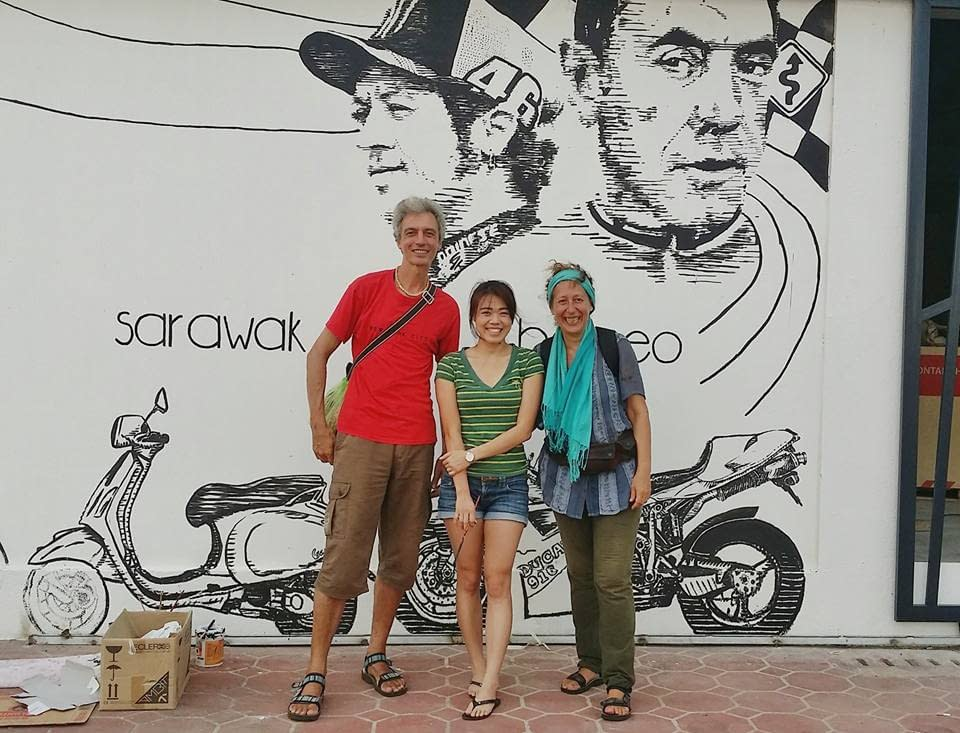 Tourists taking picture with artist of iconic line art cafe mural in Kuching