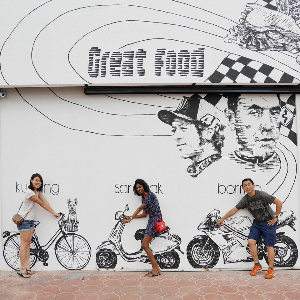 Artsy Daphy posing with iconic line art mural at feast and furious cafe Kuching