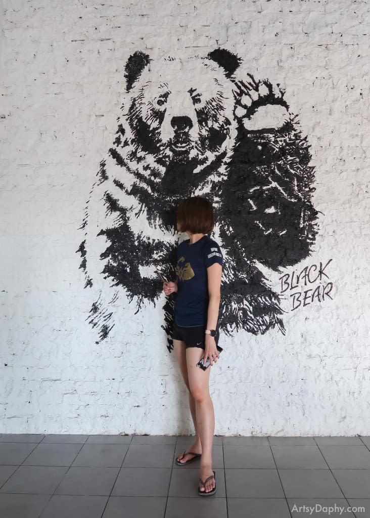 Artsy Daphy posing with Yunique black bear mural at the cafe's Emporium Kuching branch.