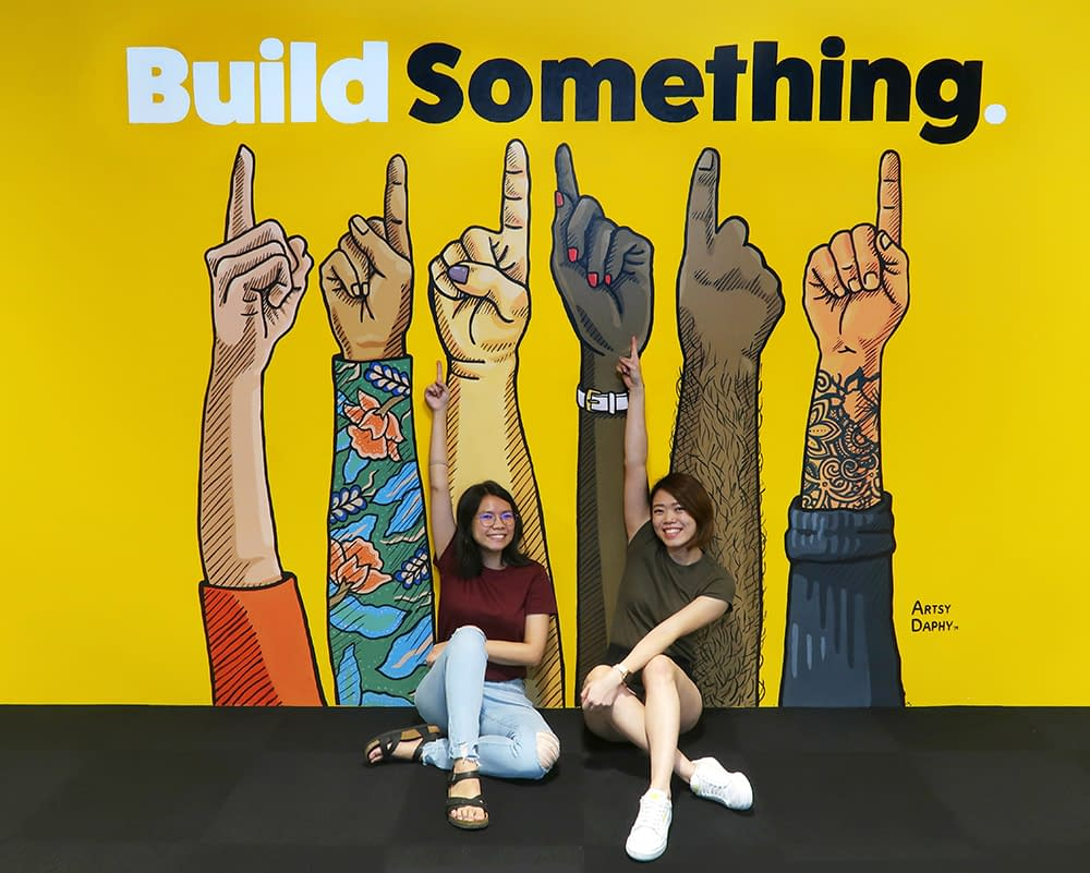 Girls posing in front of Nas Daily Office Mural featuring the words 'Build Something'