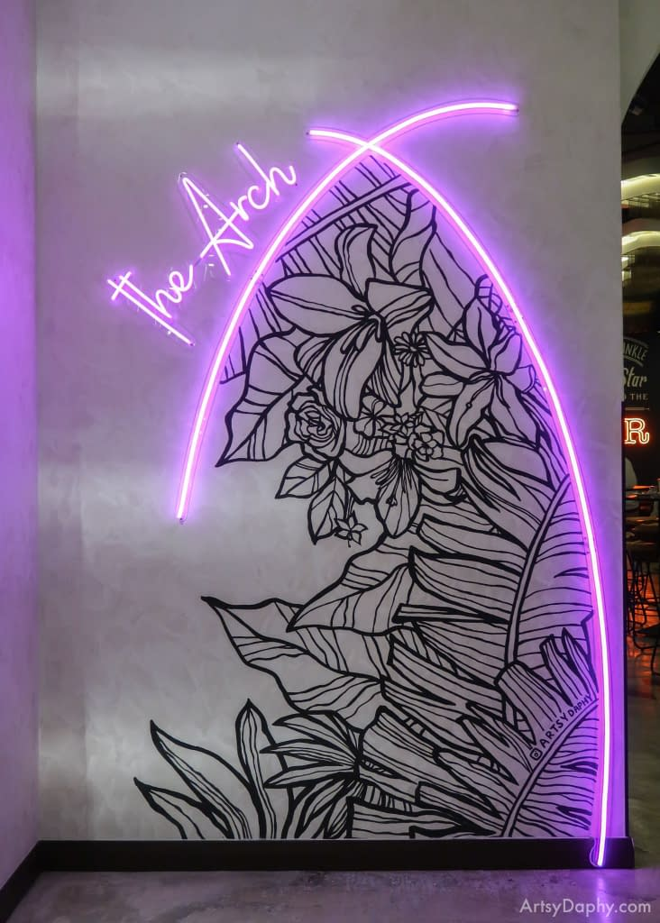 """neon light arch mixed with hand painted flower art and the typography """"the Arch"""""""
