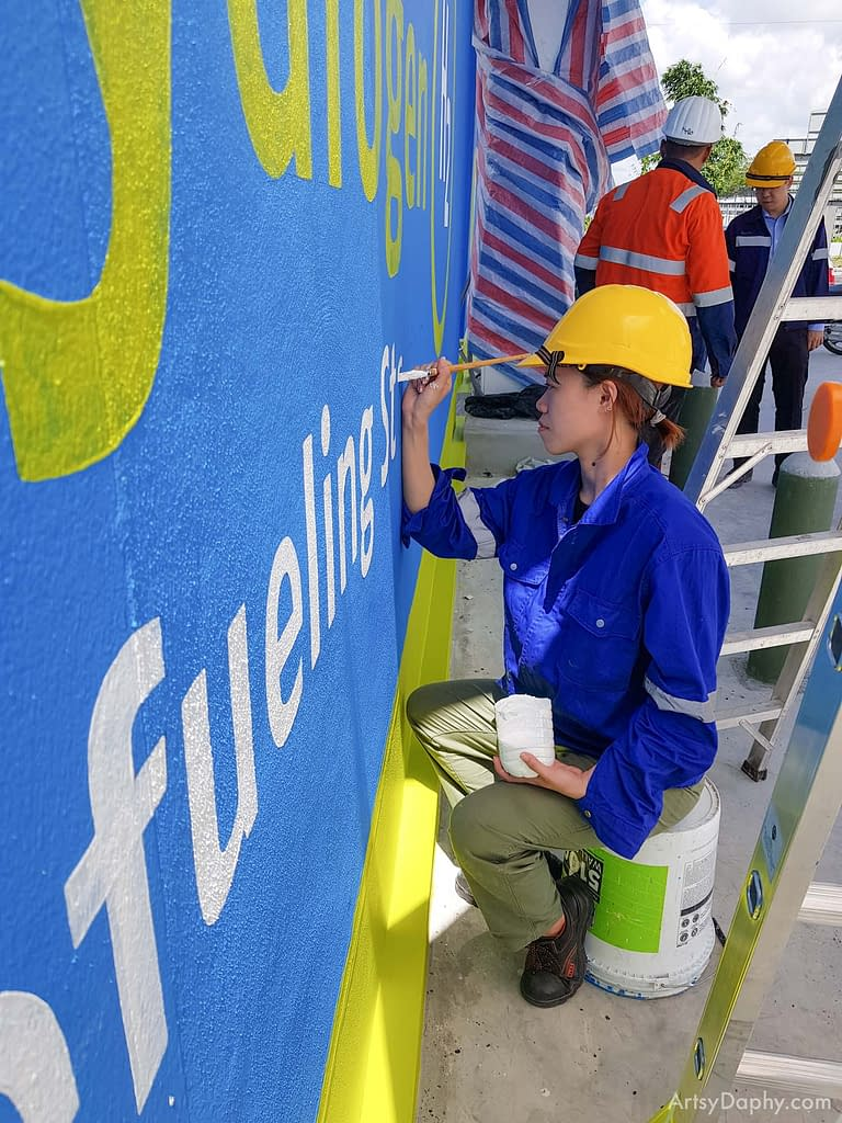 Artsy Daphy painting the Sarawak Energy Hydrogen Fuel Cell Refuelling Station Wall