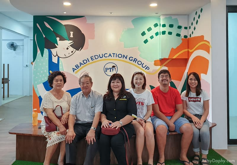 parents posing at the colourful abstract mural art at the waiting area of abadi tuition centre